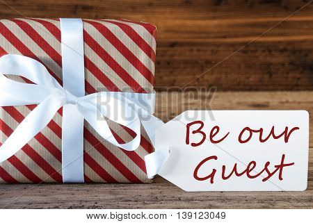 Macro Of Christmas Gift Or Present On Wooden Background. Card For Seasons Greetings, Best Wishes Or Congratulations. White Ribbon With Bow. English Text Be Our Guest