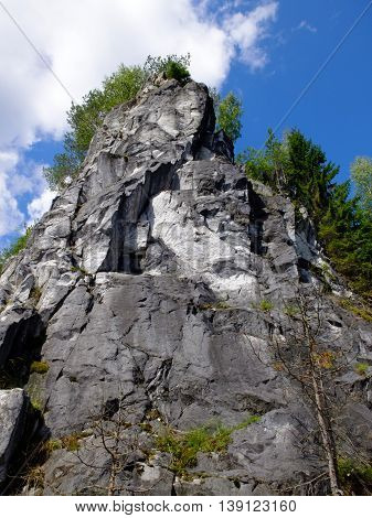 Marble high mountain. Field of white and grey marbles. Stone cliff going into the water. Landscape of mountains and sky.