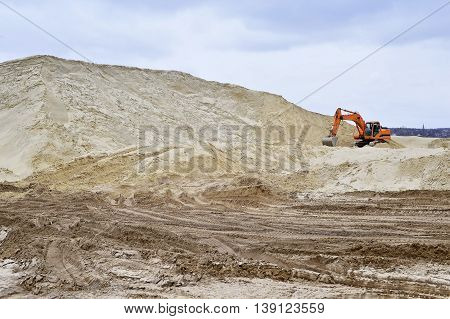 Working digger in a quarry produces sand