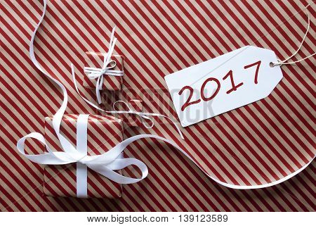 Two Gifts Or Presents With White Ribbon. Red And Brown Striped Wrapping Paper. Christmas Or Greeting Card. Label With English Text 2017 For Happy New Year