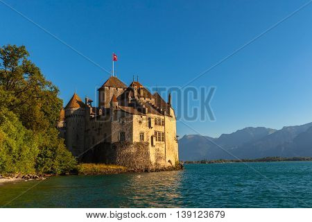 Beautiful view of Chillon castle at dusk in the golden sunshine on the lakeside of Lake Geneva Montreux Canton of Vaud Switzerland