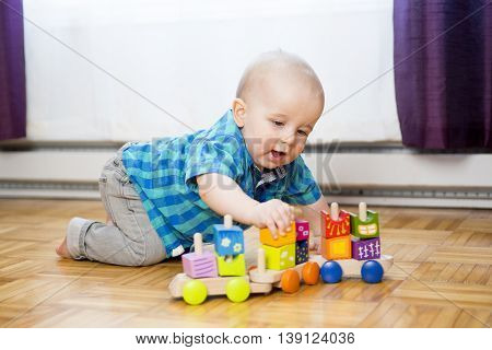 A kid toddler playing  wooden toys at home or nursery