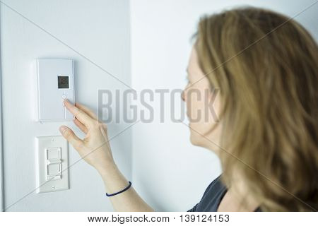 A Woman Adjusting Thermostat On Home Heating System
