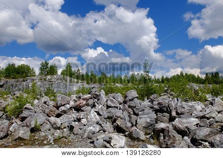 Landscape marble career collapse amid clouds of Northern nature and the place of its production. Stone material for making buildings and interior. Industrial raw materials marble.