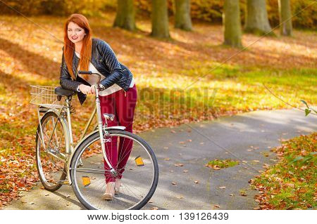 Woman on bike in park. Autumn fashionable clothing.