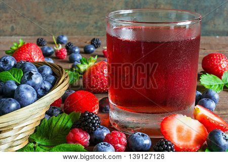fresh cold summer berries juice in a glass with ripe berries in a wicker bowl and around on rustic wooden background