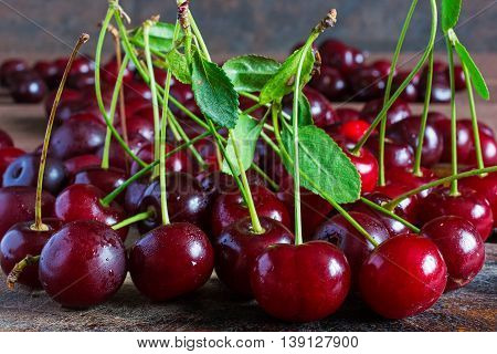 fresh cherries on stems with water drops on wooden table background summer fruit background. front view