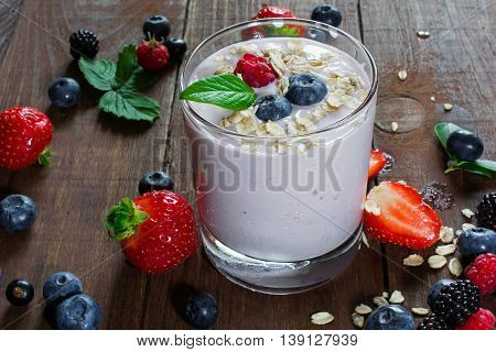 glass of fresh mixed berries granola and yogurt in a glass and ripe berries around on wooden table. healthy breakfast