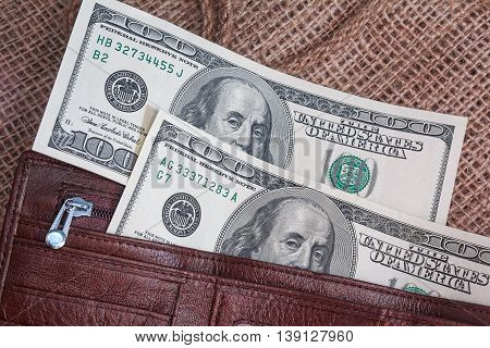 Dollar banknotes in a purse on the textile background