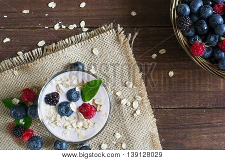 Yogurt with oatmeal or muesli and fresh berries in a glass and ripe berries in a wicker bowl. healthy breakfast. top view