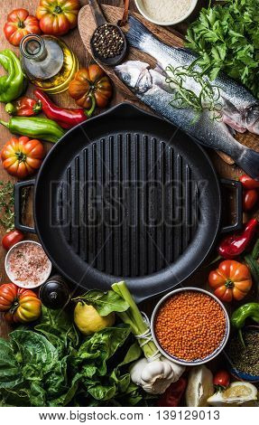 Raw uncooked seabass fish with vegetables, grains, herbs, spices and olive oil on chopping board, iron grilling pan in center with copy space, top view, vertical copmosition