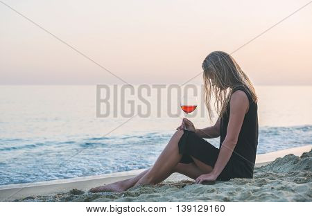 Young blond woman relaxing with glass of rose wine on beach by the sea at sunset. Cleopatra beach, Alanya, Mediterranean region, Turkey.