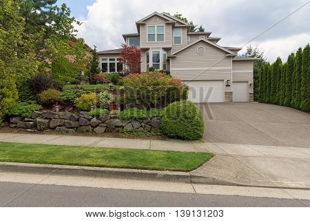 Traditional house with three car garage frontyard garden lush landscaping and green lawn in North America suburban neightborhood