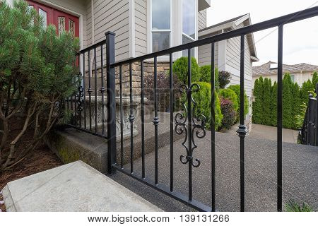 Wrought iron railings on steps to house front door entrance closeup