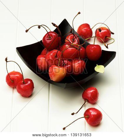Ripe Sweet Maraschino Cherries in Black Wooden Plate closeup on White Plank background