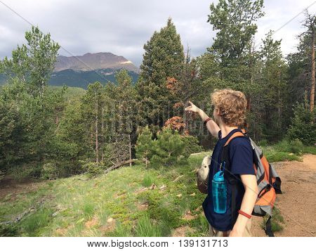 A young male hiker on Barr trail on Pikes Peak in Colorado Springs CO USA points to his destination at the summit of the mountain.