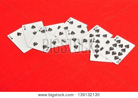 Playing card. Two to ten of spades isolated on a red background