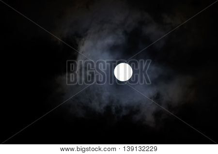 Night mysterious landscape in cold tones - full moon in the night sky and dramatic night clouds. Night sky gothic background with full moon