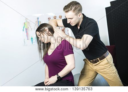 A Doctor examining his patient neck in medical office