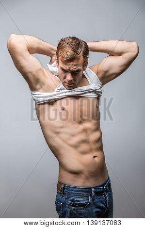 Man taking off a white singlet while standing in the studio on the gray background. His hands are behind the head. Guy wears blue jeans. Vertical.