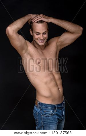 Smiling man with naked torso in  blue jeans stands on the black background in the studio. He holds his hands on the crown. Vertical low-key photo.