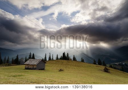 Rural landscape with dramatic sky. Autumn in the mountain village. Wooden cottage in the meadow. Storm clouds and sun rays. Carpathians, Ukraine, Europe
