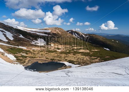 Lake in the mountains. Spring landscape with blue sky and cumulus clouds. Sunny day. The last snow on the slopes. Carpathians, Ukraine, Europe