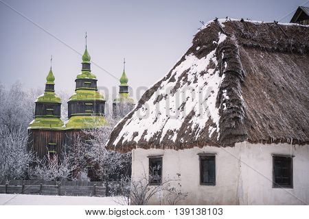 Traditional Ukrainian architecture. Old house with thatched roof and wooden church. Pirogovo museum, Kiev, Ukraine, Europe. The artistic style of photography processing. Color toning