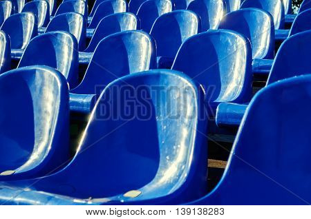 Rows of blue plastic seats in the summer park in nice sunny weather. Selective focus at the central seats.
