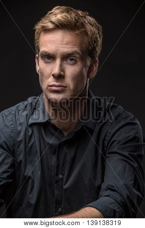 Cute guy in a dark shirt looks into the camera on the black background in the studio. Vertical low-key photo.