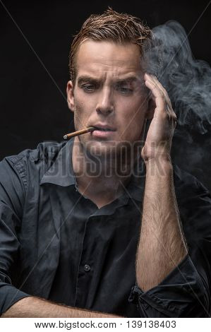 Smoking man in dark shirt on the black background in the studio. He holds the left hand near his head and looks down. Smoke swirls around him. Vertical low-key photo.