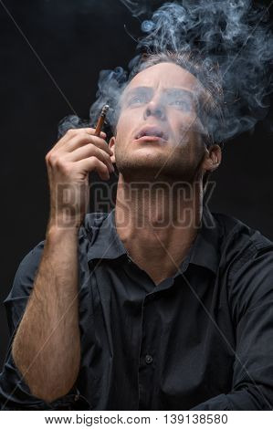 Guy in dark shirt exhales the smoke and looks up with parted lips on the black background in the studio. He holds a cigarette in the right hand. Vertical low-key photo.