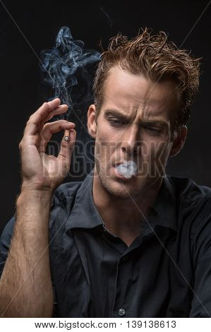 Young guy in dark shirt exhales the smoke and looks down on the black background in the studio. He holds a cigarette in the right hand. Vertical low-key photo.