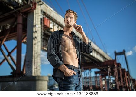 Young man in a dark unbuttoned shirt and blue jeans stands outdoors on the background of the bridge and the blue sky. He has a cigarette in the mouth. Guy looks to the right side. Horizontal.