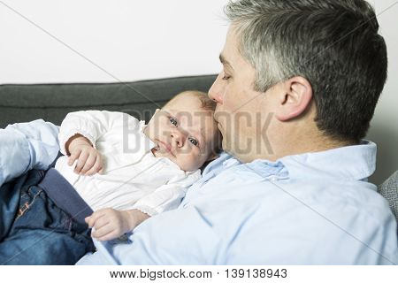 A Father holding up baby girl lying on sofa, side view