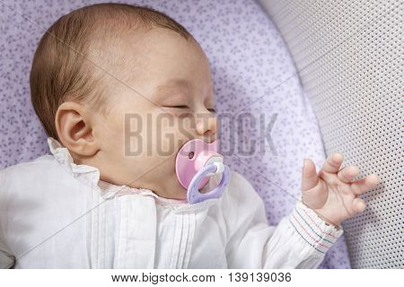 A Baby sleep in a small cradle
