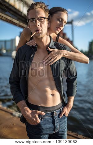 Beautiful couple stands on the quay on the background of the bridge and the river. Girl hugs the guy from behind. Man wears a dark unbuttoned shirt, jeans and glasses. He has a cigarette in the mouth.
