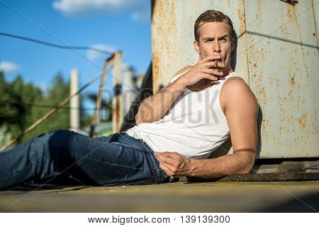 Stylish guy in a white singlet and blue jeans lies on the industrial building on the background of the blue sky. He smokes a cigarette. Man looks to the left. Outdoors. Horizontal.