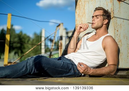 Trendy guy in a white singlet and blue jeans lies with closed eyes on the industrial building on the background of the blue sky. He smokes a cigarette. Outdoors. Horizontal.