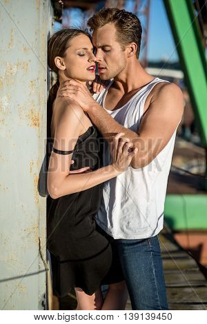 Beautiful couple shows their passion in the industrial zone. Guy wears a white singlet and blue jeans, girl wears a black dress. Outdoors. Vertical.