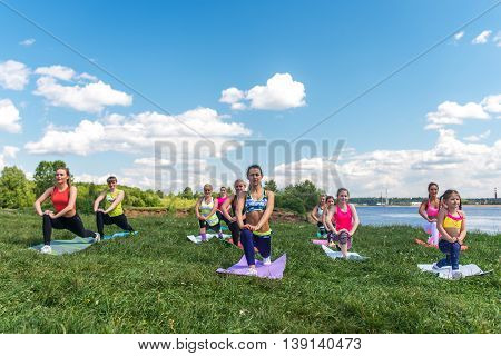 Group of women exercising and doing lunge at boot camp