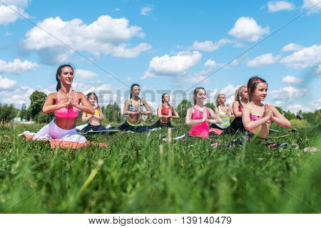 Young women stretching, warming up on aerobics class, work out outdoor