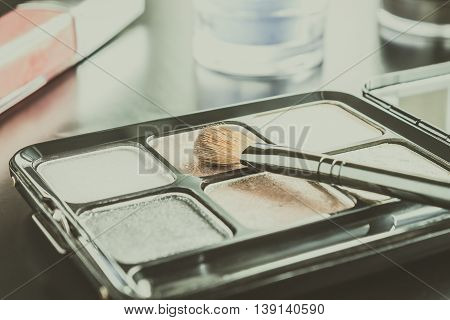 Woman cosmetics include brush and palette and eyeshadow and lip gloss on black floor classic style