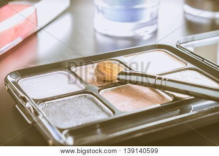 Woman cosmetics include brush and palette and eyeshadow and lip gloss on black floor vintage style