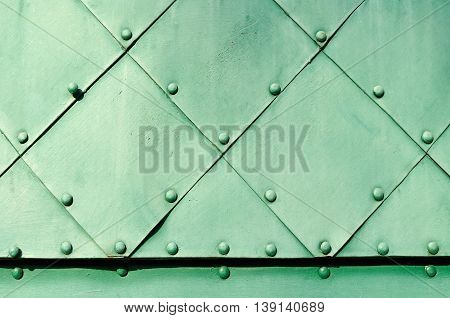 Industrial steel background. Bright green textured metallic surface of aged carved metal plates with small rivets on them.