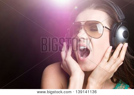 Beautiful singing woman wearing headphones