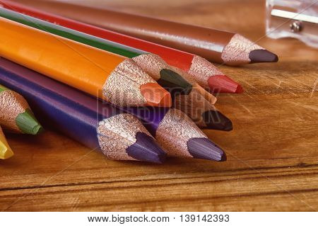 Colored pencils on a wooden surface. Group of objects close up. Pencils are located on a horizontal surface the ground slate pencils to the viewer. Indoors. Horizontal format. Color. Photo.