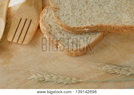 Wooden kitchen utensils with bread and barley on wooden background