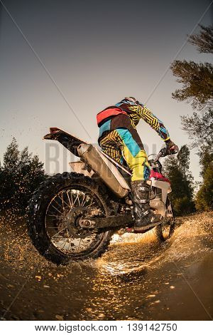 Enduro rider crossing water and muddy terrain against a beautiful sunset.