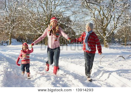 Mother Walking With Children Through Snowy Landscape